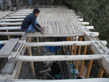 Carpenter Dadul building the ceiling with Taloo (willow twigs).