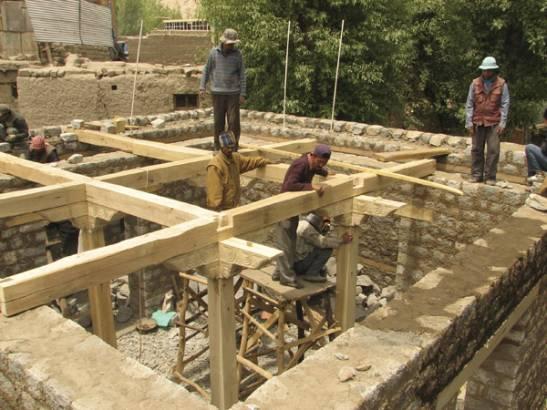 Carpenters assembling the pillars, brackets and beams.