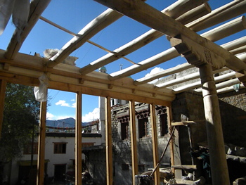 View of the rafters over beam, wall and window frame.