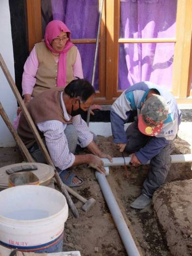 Mr Addul Masjid and wife helping install the PVC pipe at their house Choldray.