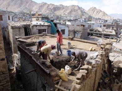THF/LOTI team mixing mud and repairing the roof of Tarchid house.