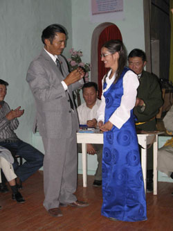 Pimpim receives an award for her work from the local governor