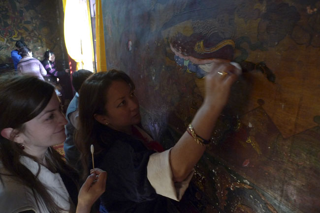 Princess Hope Leezum helping to clean the murals under supervision of restorer Anca Nicolaescu